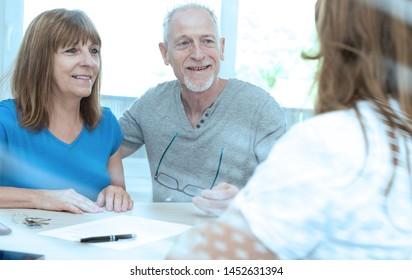 Senior couple meeting financial adviser for investment; light effect