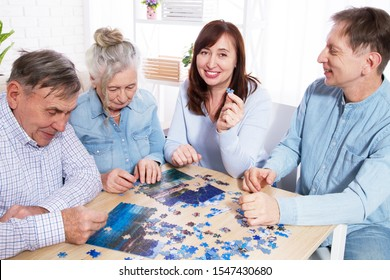 Senior couple and middle age couple solving jigsaw puzzle together with family at home