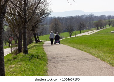 senior couple with motordriven wheelchair on blue sky sunny holiday at eastern springtime in south germany