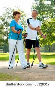 senior couple nordic walking in the park