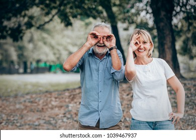 Senior couple with ok hand sign gesture on eye in the park,,Nature background