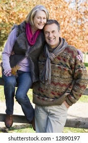 Senior couple on autumn walk with trees in background