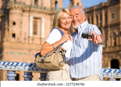 Senior couple on city break vacation taking selfie with camera