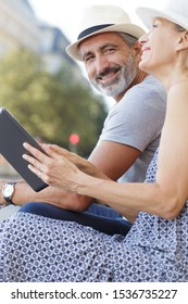 senior couple on city break using a digital tablet