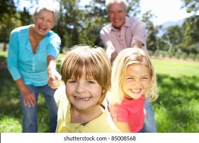 Senior couple on country walk with grandchildren