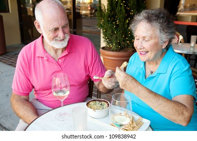 Senior couple on a date enjoys an artichoke dip appetizer.