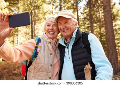 Senior couple on hike in a forest taking a selfie