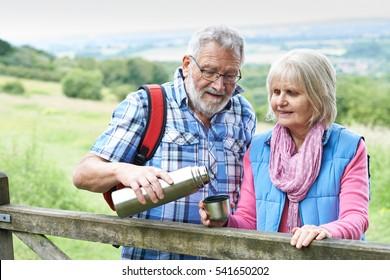Senior Couple On Hike Having Hot Drink