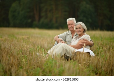Senior couple on mowed field of wheat