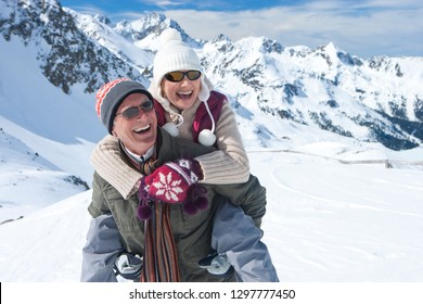 Senior couple on winter vacation with man giving woman piggyback