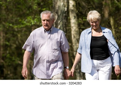 Senior couple out on a summer day strolling through the wood