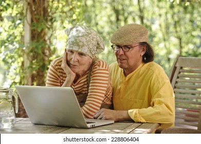 Senior couple outdoors with a laptop, They're looking at the computer. There's a sunny background of trees and bushes. Dappled sunlight from the overhead arbor filters through.