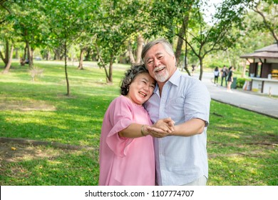 Senior couple in park. Dancing together, relaxing and loving each other with a smile