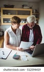 Senior couple paying bills online on laptop at home