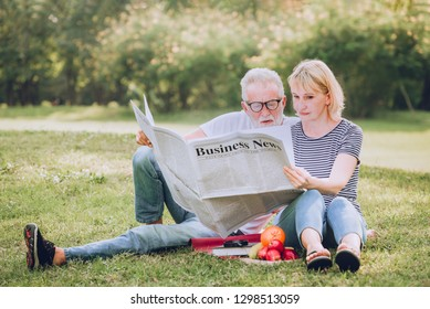 Senior couple people reading business newspaper in park.