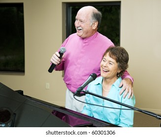 Senior couple performing a song together.  She plays piano.