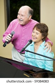 Senior couple performs.  They both sing while she plays piano.