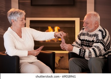 Senior couple playing cards on winter night in front of fireplace.?