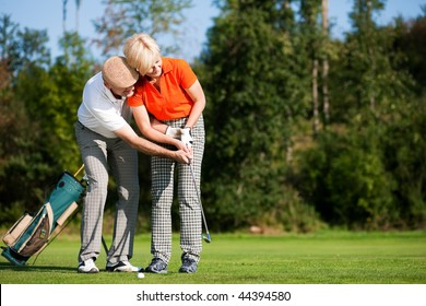 senior couple playing golf on a summer afternoon, the mal partner is trainer to the female golfer