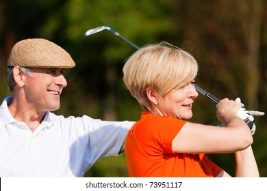 senior couple playing golf on a summer afternoon, the male partner is trainer to the female golfer