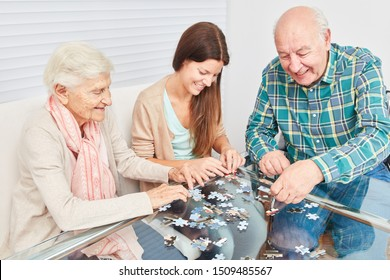 Senior couple playing jigsaw puzzle against dementia with young woman in retirement home