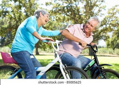 Senior couple playing on children's bikes
