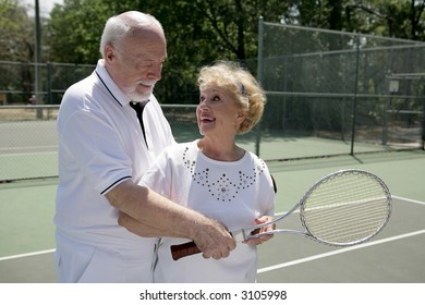 A senior couple playing tennis together.  He's showing her how to grip her racquet.