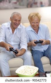 Senior couple playing video games holding joysticks.