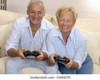 Senior couple playing video games holding joysticks.