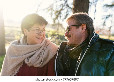 Senior couple portrait having fun together outdoors in the park, winter time.