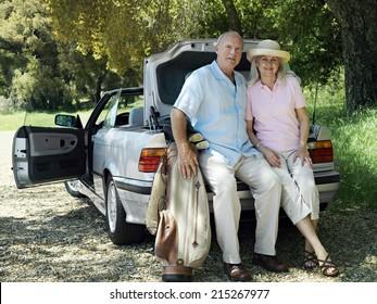 Senior couple posing beside car boot, man holding golf bag, smiling, portrait
