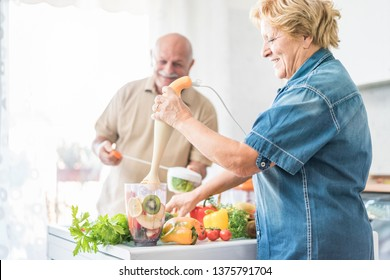 Senior couple preparing vegan smoothie with organic fruits and vegatables - Old people having vegetarian breakfast for healthy lifestyle - Healthcare concept - Focus on fruits inside blender