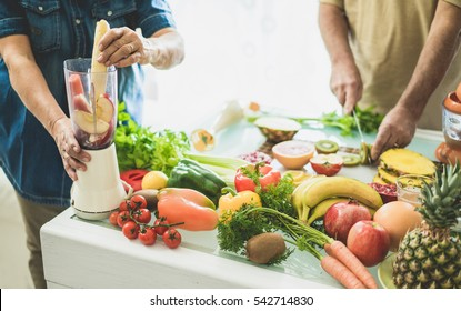 Senior couple preparing vegan smoothie with bio fruits and vegetables - Old people having vegetarian breakfast for healthy lifestyle - Healthcare concept - Warm raw filter