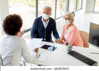 Senior couple with protective facial masks receive news from black female doctor in the office