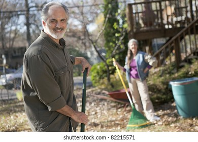Senior couple raking autumn leaves