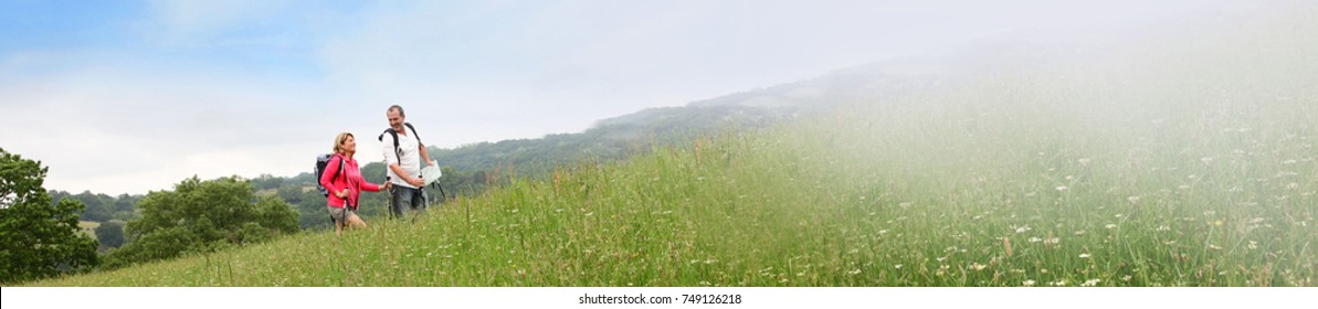 Senior couple rambling in countryside - banner template web