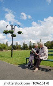 Senior couple reading a newspaper on a park bench