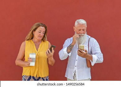 A senior couple reading their smart phones. She is holding a cardboard cup.