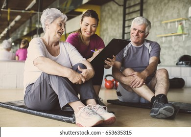 Senior couple in rehabilitation center. Personal trainer writing records exercises