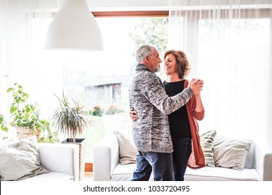 Senior couple relaxing at home, dancing.