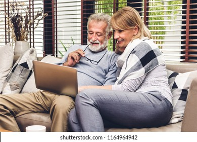 Senior couple relaxing and using laptop computer together sitting on sofa in living room at home.Retirement couple concept