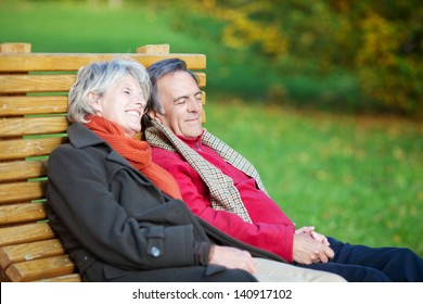 Senior couple resting holding hands in the park