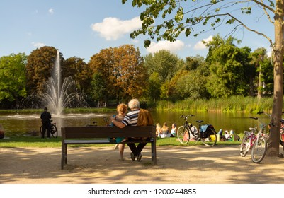 Senior couple resting on the bench at park with some Young People and Bikes as an Autumn scene.