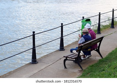 Senior couple resting on a bench near the river on a summer evening in Cluj-Napoca, Romania on September 8, 2020