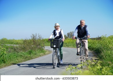 Senior couple riding bike together on country road
