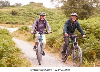 Senior couple riding mountain bikes in a country lane during a camping holiday smiling, front view
