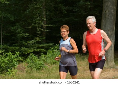 senior couple running in the woods