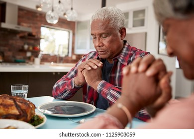 Senior Couple Saying Grace Before Meal Around Table At Home
