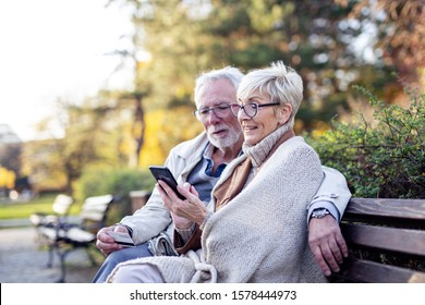 Senior couple shopping on line with mobile phone and credit card while sitting on the bench in park