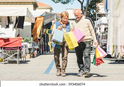 Senior couple shopping together at flea market with wife watching in husband bags - Active elderly concept with mature man and woman having fun in city - Happy retired people moments on vivid colors